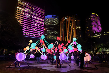 touched: SYDNEY, AUSTRALIA, MAY 27, 2015:  Tourists and local public enjoy the Affinity installation at Vivid Sydney, which  depict the  human brain and neurons.  When touched, the orbs set-up a striking display of sound and light.  People in motion.  Artists:  am Editorial