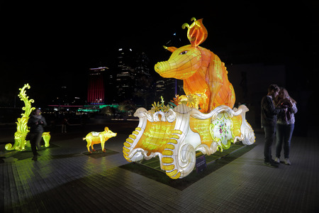 greedy: SYDNEY, AUSTRALIA - MAY 25, 2015;  Entitle - a chinese lantern installation for Vivid Sydney is all abour overindulgence and the greedy pig.  People wander aound the installation taking photos late at night