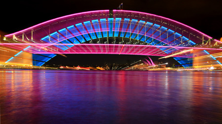 rainbow bridge: SYDNEY, AUSTRALIA - JUNE 3, 2013;  Sydney Harbour Bridge lit for Vivid Sydney and with a camera zoom effect and spectacular reflections in the harbour water.  Hues of pink and blue Editorial