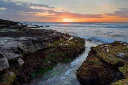 soothing: Dawn breathes its first light upon the land as the rhythym of the ocean  brings soothing sounds along the broken shoreline Stock Photo