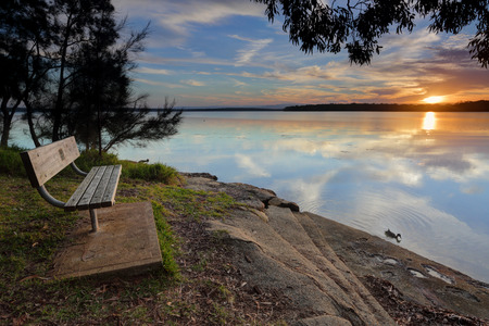 georges: Seat with a beautiful tranquil water and sunset view in St Georges Basin, Australia