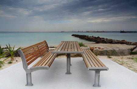 table and chairs: Silver Beach, Kurnell on Botany Bay, Australia is lined with stone groynes to protect beach erosion.  Picnic bench and seat in foreground.