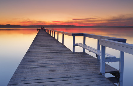 jetty: After sunset at Long Jetty, fiery red clouds and reflections in Tuggerah Lake, Central Coast NSW, Australia