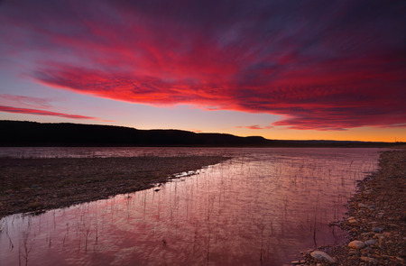 brisk: Brisk and windy winter sunset sky and reflections over Lake Burralow in Penrith, Australia