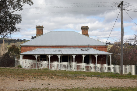 bygone: Old run down Australian house with corrugated iron roof, verandah with fancywork and  white picket fence in rural countryside scene.  A bygone era. Editorial