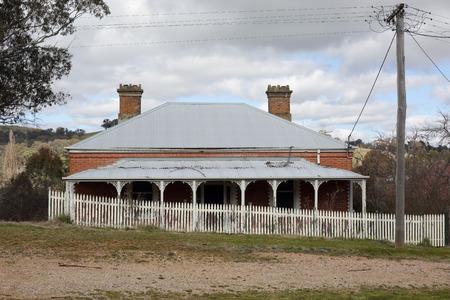campagne rural: Vieux d�labr� maison australienne avec un toit en t�le ondul�e, v�randa avec fancywork et cl�ture blanche dans la sc�ne de la campagne rurale. Une �poque r�volue.