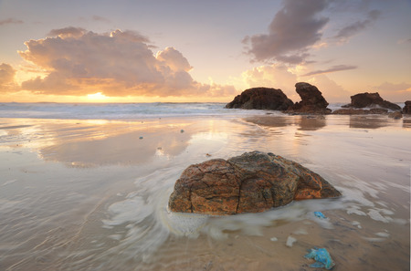 blubber: Summers sunrise at Lighthouse Beach Port Macquarie on mid north coast Australia.   A high tide brought in blue jelly blubber jellyfish.  There is motion in the tidal flows Stock Photo