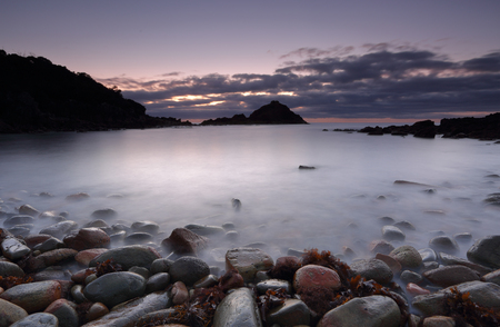 south coast: Dawn skies pre sunrise long exposure and cool colours at Mimosa Rocks, Aragunnu.  This little bay foreshore is full of pebbles and no sand.  Stones range in size and colour.  Far south coast NSW, Australia Stock Photo