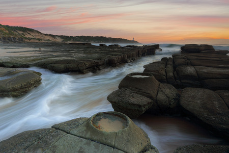 chasm: Ocean flowing in and out of the rock chasm at Soldiers Point Norah Head Stock Photo