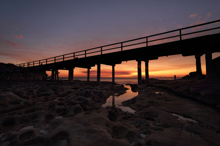 la: The eroded cratered rocks under the bridge at Bare Island,  La Perouse Botany Bay as the sun sets Stock Photo