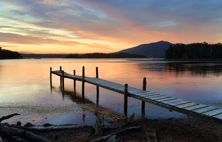 rickety: This old rickety timber plank jetty juts out into Wallaga Lake, the largest lake in southern NSW.  The sunset beyond painting the sky and colouring the tranquil waters in soft hues of red and blue.  Mt Gulaga rises in the distance and Merriman Island lies