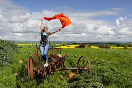 country life: A woman on an old rusted tractor plough enjoying country life.  Wellness, fun