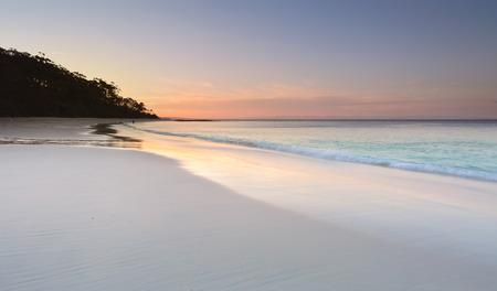 Sereniteit en rust bij zonsondergang op Murrays Beach in Booderee National Park, Jervis Bay Australië. Mooie zachte kleuren in de lucht en reflecteren in het natte zand. Een rustige plek om te ontspannen van de drukte of problemen van het leven Stockfoto - 47422761
