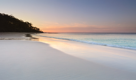 Serenity and peace at sundown on Murrays Beach in Booderee National Park, Jervis Bay Australia.  Pretty soft colours in the sky and reflecting in the wet sand.  A tranquil place to unwind from lifes busyness or troubles