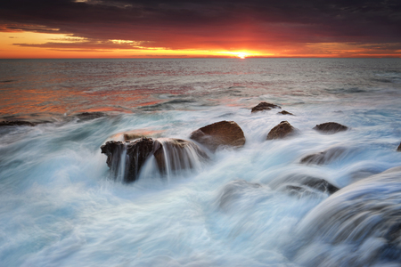 whitewater: Waves crash over rocks creating torrents of whitewater and waterfalls over rocks at sunrise.