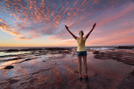 jubilation: Woman with arms outstretched towards the sunrise sky celebrating life.  Jubilation, triumph, success, spiritual, exhilaration, Stock Photo