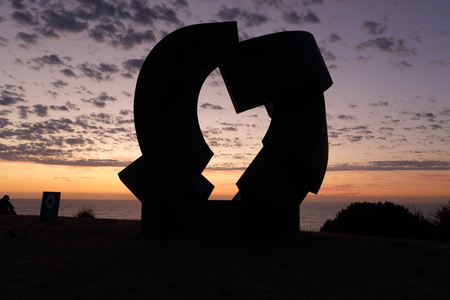corten: BONDI, AUSTRALIA - OCTOBER 25, 2015;  Annual Sculpture by the Sea free public event.  Exhibit titled Divided Planet by Jorg Plickat is made of corten steel silhouetted against a pretty dawn sky on Biondi coastline Editorial