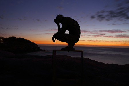 titled: BONDI, AUSTRALIA - OCTOBER 25, 2015;  Annual Sculpture by the Sea free public event.  Exhibit titled Crouching Man by Laurence Edwards.    Made of bronze. Silhouette against dawn sky Editorial