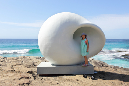 joys: BONDI, AUSTRALIA - OCTOBER 25, 2015;  The joys of visiting the annual Sculpure by the Sea event is to experience each individual display piece and the myriad of photo opportunities  in and around them.  Here a girl has her photo taken at the installation