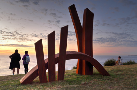 linda: BONDI, AUSTRALIA - OCTOBER 25, 2015;  Annual Sculpture by the Sea  public event.  Exhibit titled The Bridge by Linda Bowden, made of Corten Steel being lit by the first light of the rising sun. Editorial