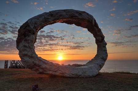 titled: BONDI, AUSTRALIA - OCTOBER 25, 2015;  Annual Sculpture by the Sea free public event.  Exhibit titled Open by Peter Lundberg made of cast concrete with early morning sunlight touching its eastern face