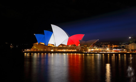 extremist: SYDNEY, AUSTRALIA - NOVEMBER 16, 2015;  Sydney Opera House lit up in colours of the French flag... blue, white and red in support of mulitple tragic terrorist events in France  by an islamic extremist group named ISIS