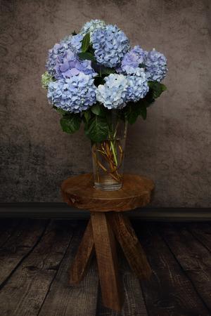 madera rústica: Hydrangea flores del jardín cortar y dispuestos en un florero de cristal y sentado en una mesa taburete de madera rústica. Decoración del hogar, primavera, flores