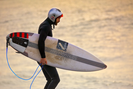 notorious: CAPE SOLANDER, AUSTRALIA - AUGUST 27, 2015; Surfer wearing a gath surf helmet and wetsuit and carrying a surfboard at sunrise while  at the notorious reef break at Cape Solander where only the best and bravest surf.  The helmet has many scratches