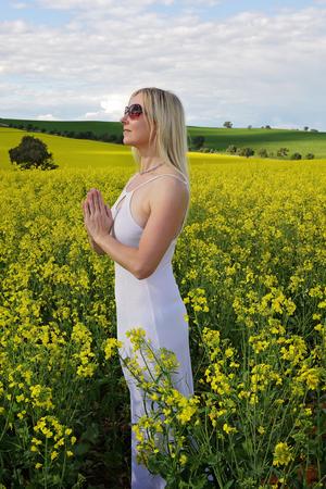 madre tierra: Mujer que ruega a Dios o de la madre tierra por la lluvia o la cosecha abundante o ella podr�a cinco meditando en la naturaleza etc. De pie en un campo de canola dorado y con un vestido blanco puro Foto de archivo
