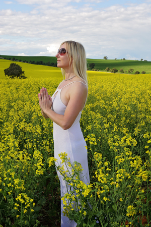 abundant: Woman praying to God or mother earth for rain or abundant harvest or she could ve meditating among nature etc.  Standing in a field of golden canola and wearing a pure white dress Stock Photo