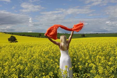 abundant: Happy woman wearing a long white dress and with scarf flailing in the air standing in a field of golden canola in rural Australia