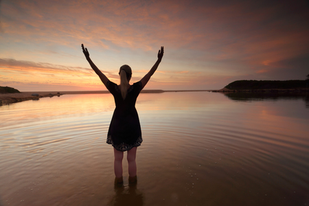 woman beach dress: A woman with arms outstretched towards the sky in an act of success, praise of mother nature, or  worship of spirituality or religion on an amazing sunrise morning.  Dee Why Lagoon, Australia