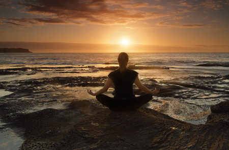 spirituality: Female sitting by the ocean at sunrise meditating, wellness, health, spirituality.
