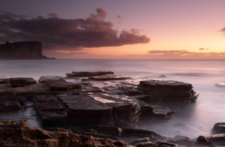 hint: A long exposure at dawn down on the rocks at Avalon with a hint of golden light emerging before sunrise. Stock Photo