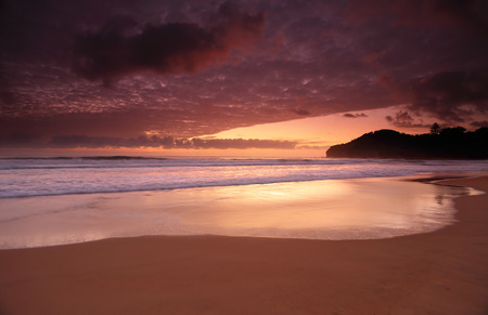sensational: Standing near the northern end of Warriewood Beach as the dawn skies colour before an amazing sunrise.  Long exposure with motion in water. Stock Photo
