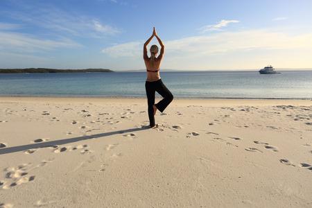 Frau ausgewogen in einer Yoga-Pose barfuß auf einem Bein mit den Händen über dem Kopf am Strand in der späten Nachmittag Sonne verbunden, auf dem Sand lange Schatten Zeichnen. Asana vrksasana. Standard-Bild