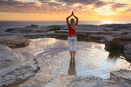 quiet scenery: A woman standing by the ocean at sunrise, practicing yoga, meditation, pose.  Rejuvenating the soul, quiet time and solitude in natures beautiful surrounds. Stock Photo