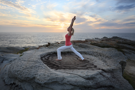 arms above head: A female lunges forward while stretching the other leg and arms straight above her head as a yoga pilates routine by the sea. A variation of anjaneyasana, ashwa sanchalasana.