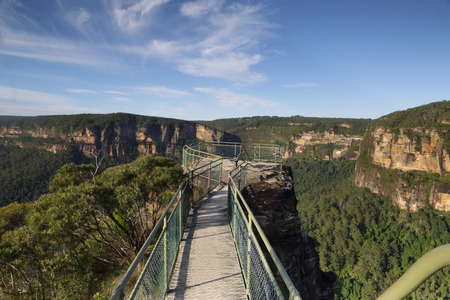 bushwalk: A small narrow bridge helps your traverse the narrow precipice with safety to one of the lookout posts.   A further steep ladder takes you down onto a lower smaller ledge and lookout.  Vigorous movement in the tree along the bridge shows just has gusty it Stock Photo