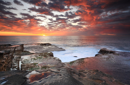 mosses: Stunning sunrise over Maroubra, rich colours in the sky and their reflections as water flows over and around rocks.  Some motion in the retreating water and mosses.
