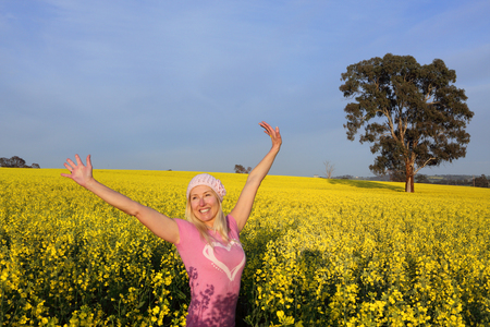 exuberant: Happy smiling exuberant woman in a field of golden canola with arms raised above her head in the early morning sunshine