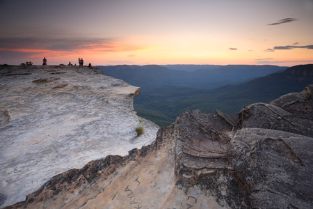 Sunset views west from Lincoln Rock in the Blue Mountains, Australia. Visitors carve names and words into the rock platform and the entire platform is littered with etchings. People in the far distance are blurred beyond recognition.
