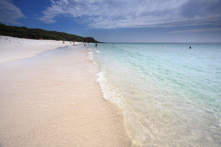 paradise bay: A touch of paradise at Jervis Bay Australia.   Mid morning on a beautiful summer day with the sun streaming through the clouds.  All people in the far distance are unrecognisable
