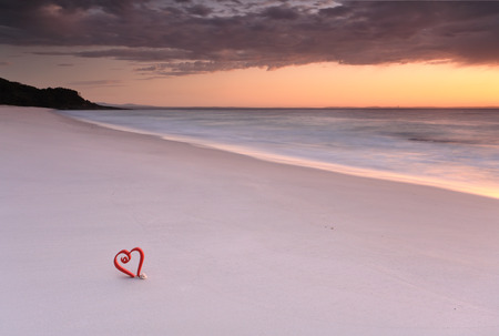 hues: Love Jervis Bay, Australia, Soft hues of dawn and a lone red heart in the sand at the beautiful beaches of Jervis Bay Stock Photo