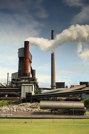 Steel mill smelter emitting toxic fumes and air pollutants billowing up and out of one of its many tall chimneys.  Pollutants can vary and include hydrogen fluoride, sulfur dioxide, oxides of nitrogen, offensive and noxious smoke fumes, vapors, gases, and