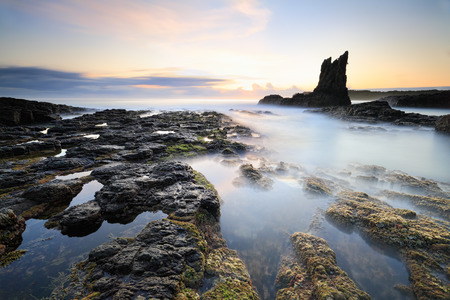 resemblance: Cathedral Rock, in Kiama, south coast NSW, has a definite resemblance to a cathedral or church.  Long exposure calms the waves creating a surreal place.   A rock pile ceases to be a rock pile the moment a single man contemplates it, bearing within him the Stock Photo