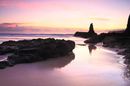 kiama: Beautiful sunrise skies and reflected colours in the tidal wet sands.  Jones Beach, Kiama Downs Australia Stock Photo