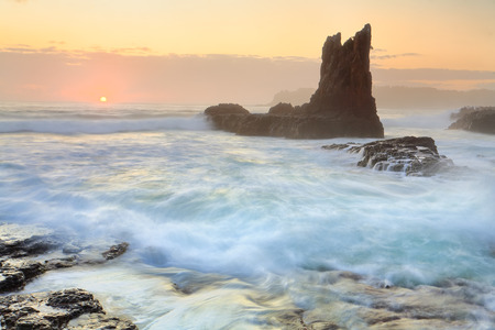The new day sun glimpses over the horizon at Cathedral Rock, Kiama, Australia.  A sea mist or fog obscures clarity but softens the scene.