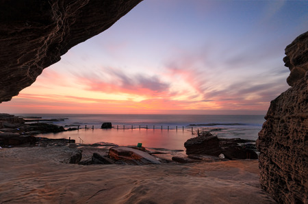 sensational: Sensational sunrise at Mahon rock pool, Maroubra, bathing the rocks and pool in vibrant reds and pink hues while a cave adds some interesting textures and framing to the scene.