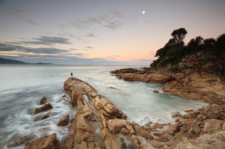 nsw: Dusk light at Bermagui, south coast NSW Australia with the ocean swirling around a finger rock protruding from the shore and lone fisherman standing at its farthest edge in the distance. Stock Photo